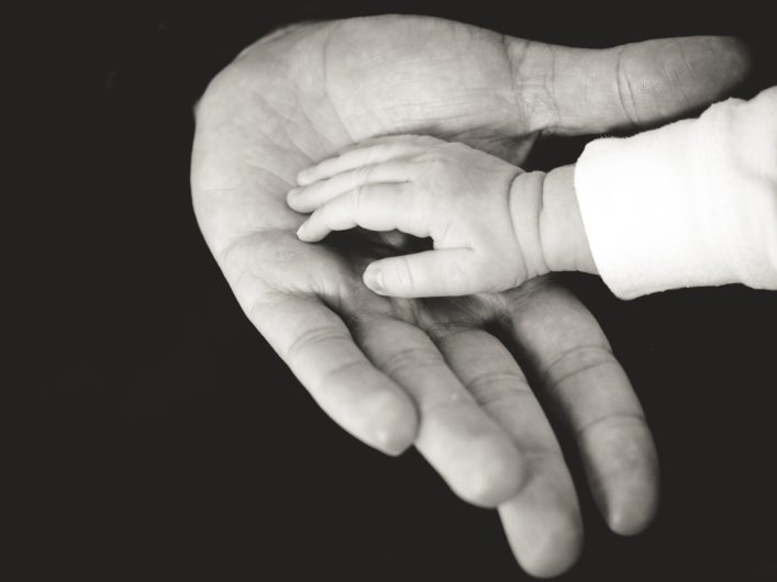 A baby holds a parent's hand.