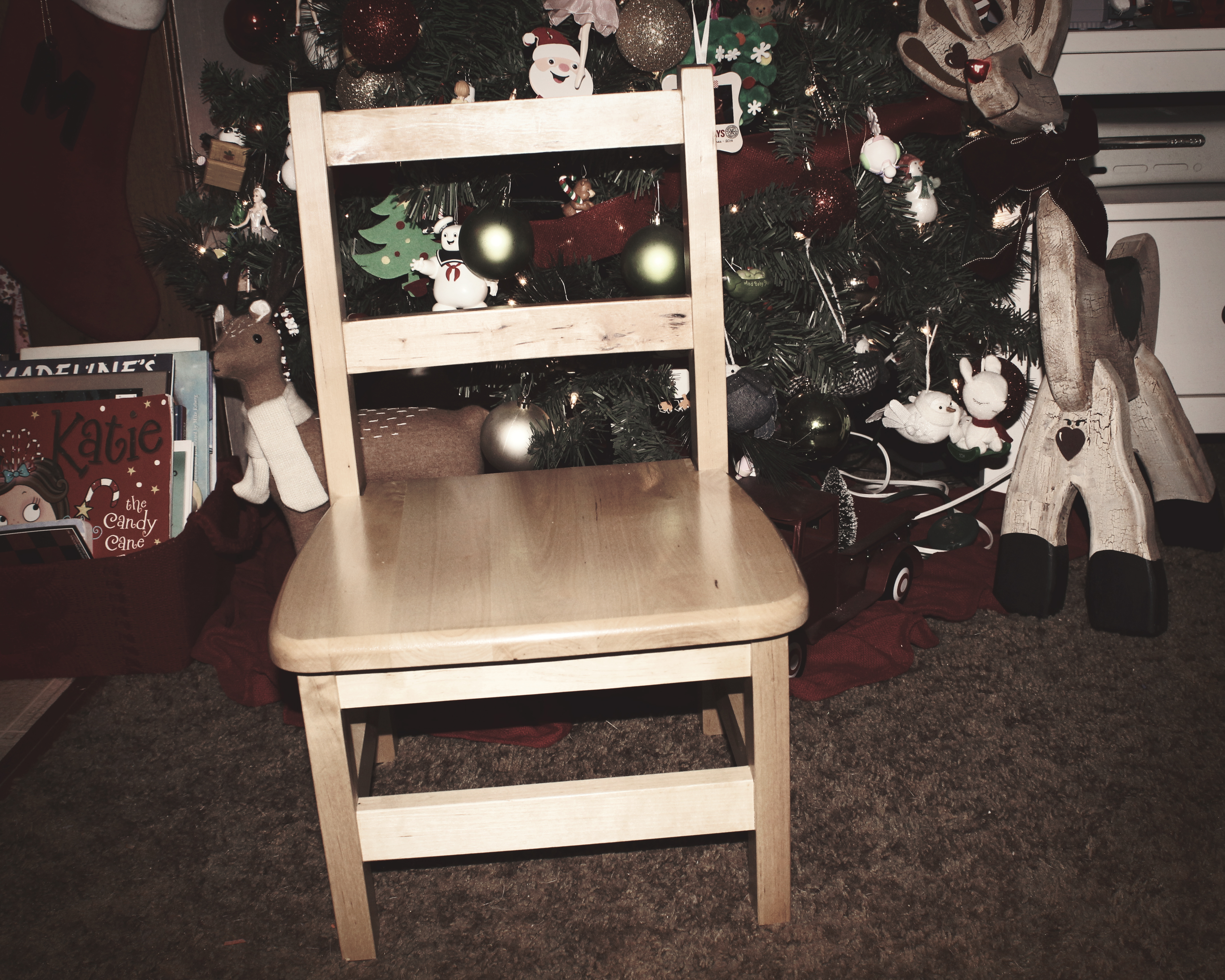 An empty chair in front of Christmas Tree