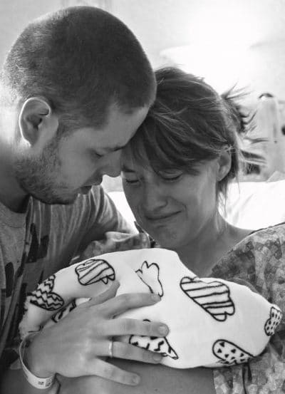 parents holding a small infant that passed away