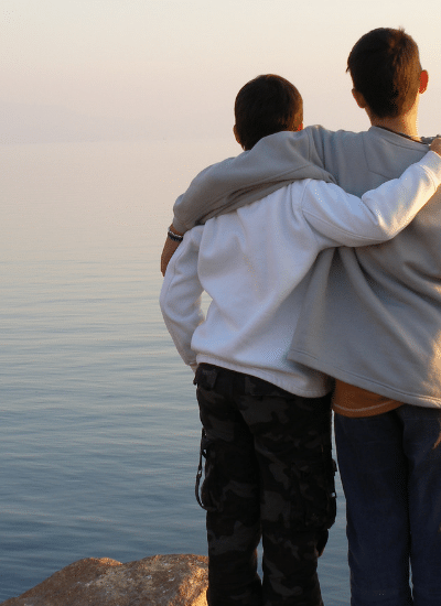 two boys looking at water