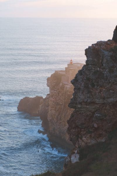 woman sitting on cliff watching ocean