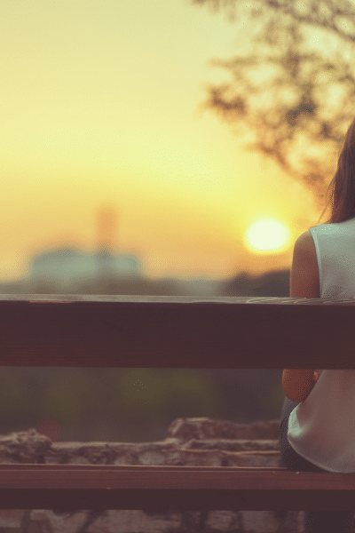 woman sitting on park bench as sun sets