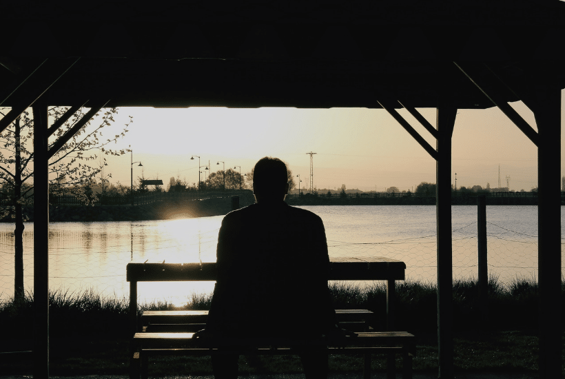woman sitting on bench watching sun