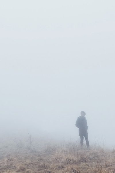 Person standing in fog on a hill