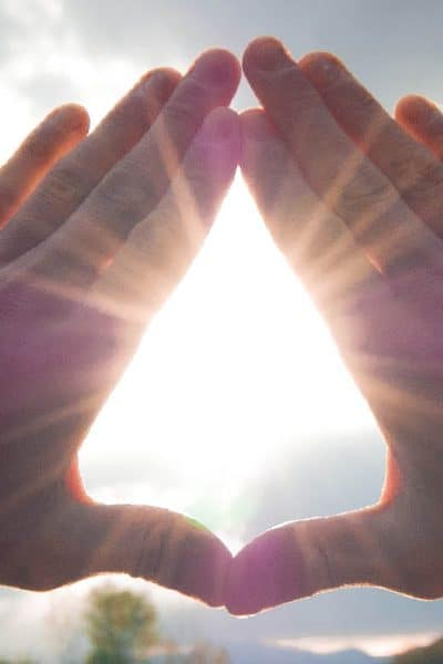 Looking at beauty of sunlight through hands making a diamond shape