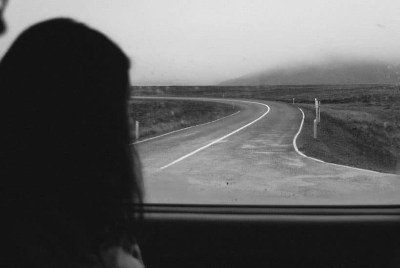 Woman looking out at a winding road