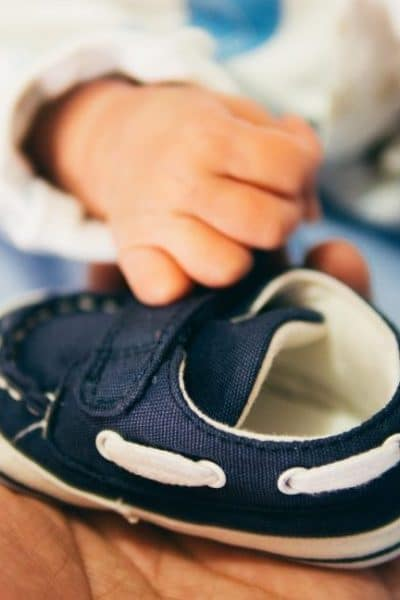 infant and a hand holding a blue shoe