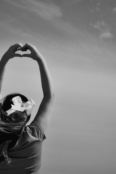black and white of woman holding up hands in heart shape
