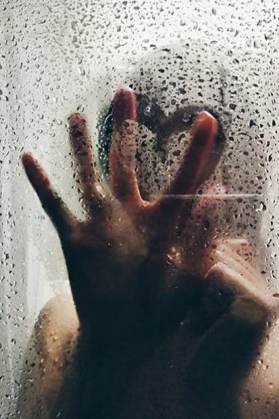 Woman pressing hand against a shower door