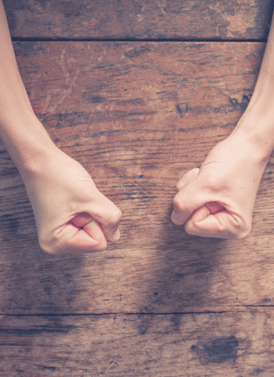 Female fists on a wooden table