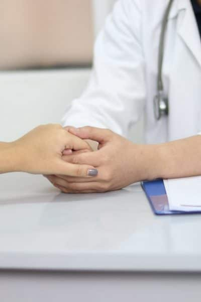medical professional holding hand of a woman