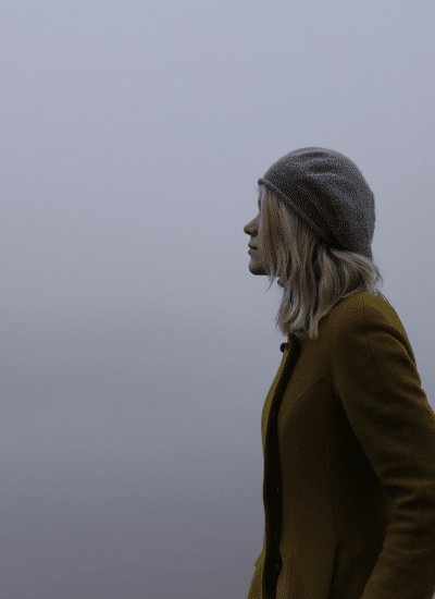 woman in hat standing near fog