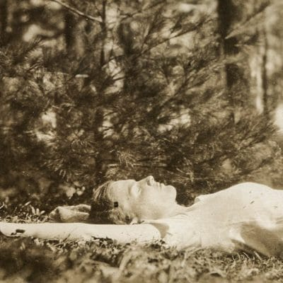woman lying on ground in forest