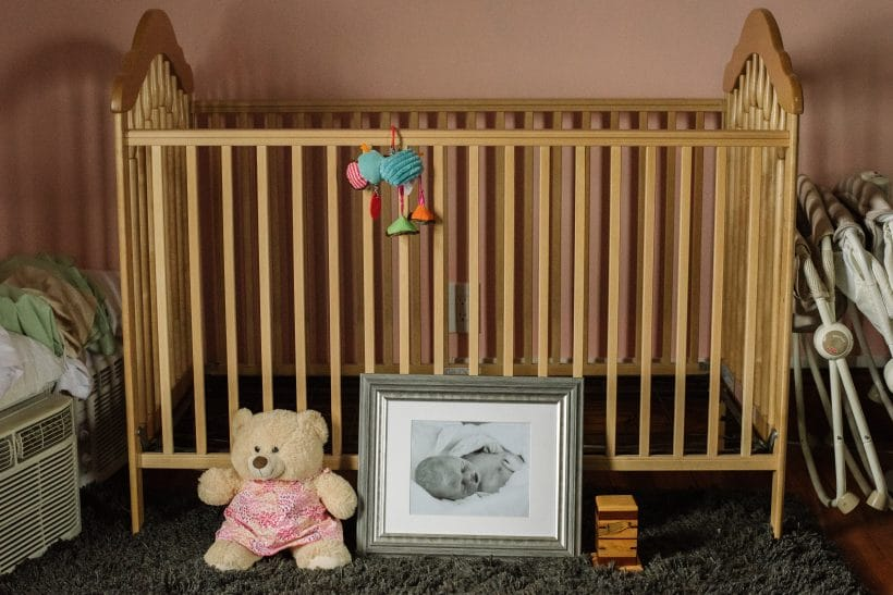 Abby's photo sits in front of her empty crib with the keepsake bear designed in her memory.