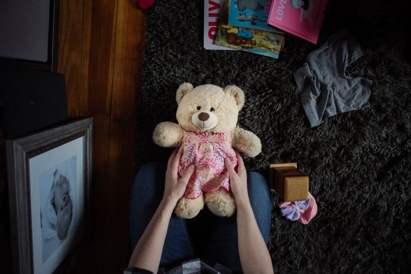 A mother holds a keepsake bear next to the photo of her stillborn daughter.