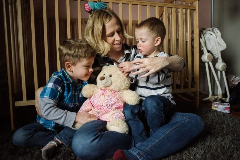 Kristin Naylor's sons sit in her lap with a keepsake bear representing their sister, Abby.