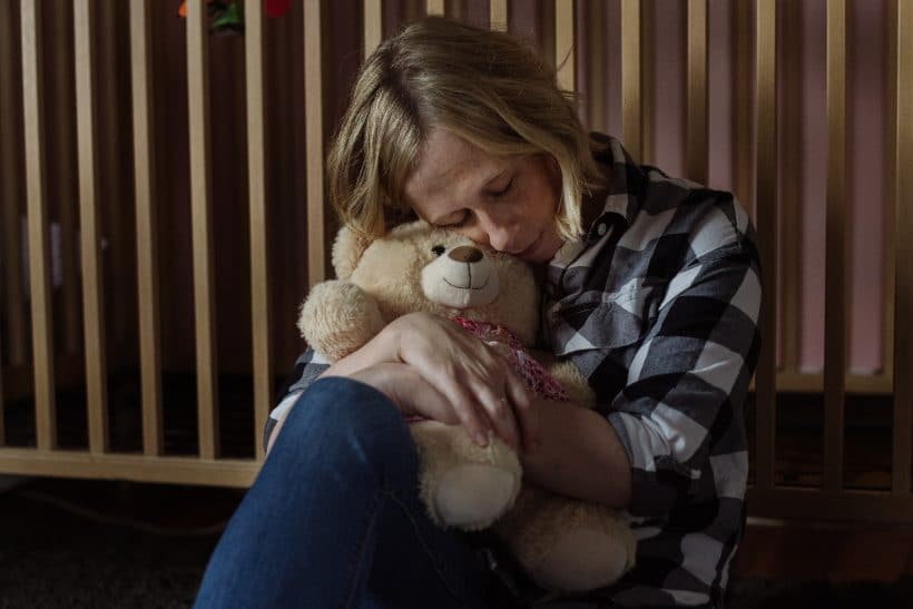 Kristin Naylor hugs the keepsake bear designed to honor her daughter, Abby who was stillborn.
