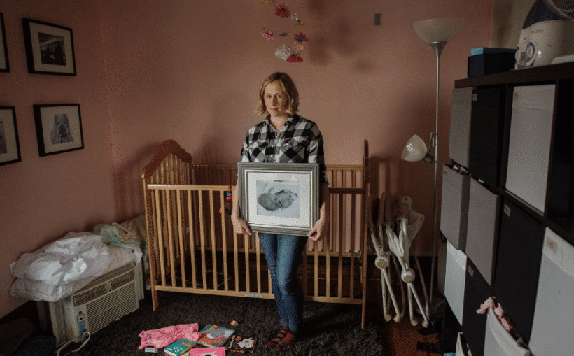 Kristin Naylor holds a photo of her stillborn daughter in the empty nursery.