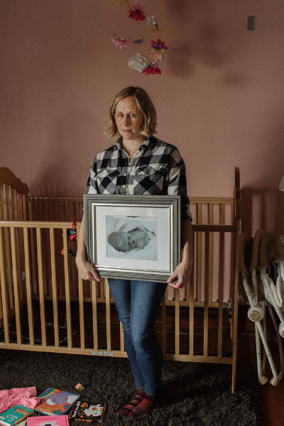 Kristin Naylor holds a photo of her daughter Abby who was stillborn while standing in Abby's empty nursery.