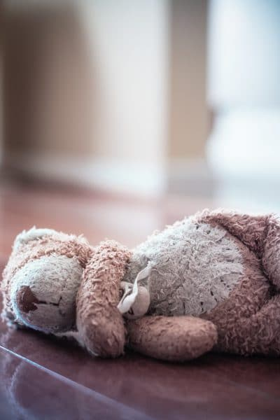 Forlorn old worn teddy bear left in empty room