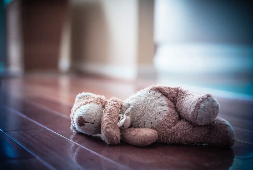 Forlorn old worn teddy bear left in empty room