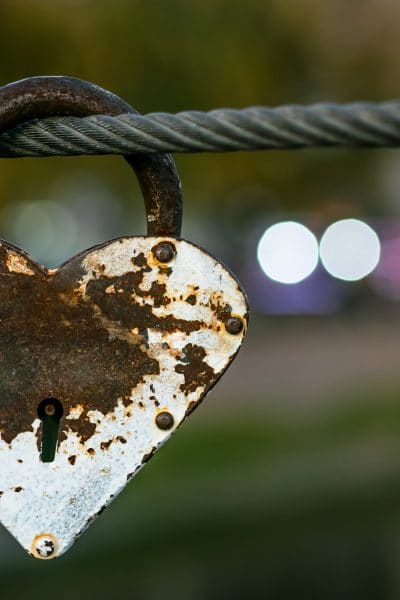 Heart shaped heavy rusty antique lock on urban street background. Vintage padlock on rope. Romantic love concept, fading away feelings of love.